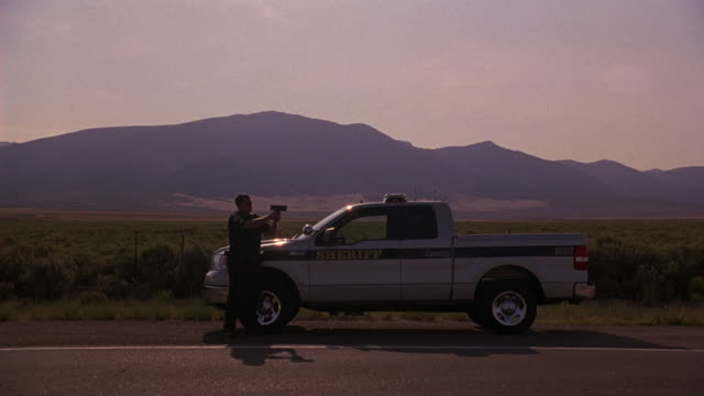 """vídeos de stock e filmes b-roll de wide angle of sheriff or police officer or cop with radar gun pointed at highway. standing next to police pickup truck or police car with writing: """"county sheriff."""" tall grass and mountains in bg. prairie landscape. - radar"""
