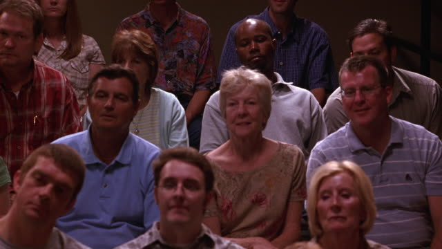 medium angle of men and women of different ages seated in television studio audience listening to speaker or lecturer (not in shot). people nod. - television show stock videos & royalty-free footage