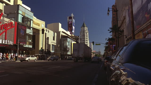 """wide angle of hollywood blvd. cars and semi truck drive on street. """"wiener mobile"""" or van with giant hot dog on top drives toward camera. - the dolby theatre stock videos & royalty-free footage"""