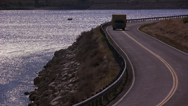 WIDE ANGLE OF WINDING ROAD NEXT TO LAKE. ROCKS ON HILLSIDE. GOLDEN WHEAT OR TALL GRASS AND BUSHES NEXT TO ROAD. CUSTOMIZED VAN OR VEHICLE, POSSIBLY USED FOR ADVERTISEMENT OR PRIVATE BUSINESS DRIVES ALONG ROAD. PAN TO FOLLOW VAN.