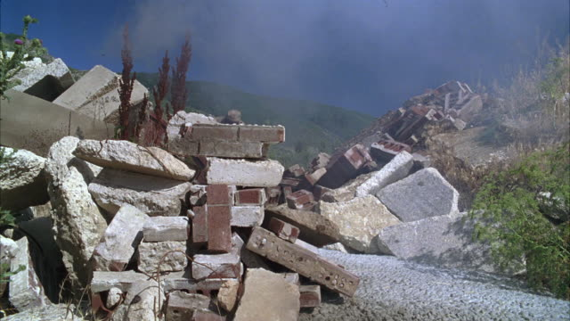 WIDE ANGLE OF SOLDIER OR GUERRILLA IN CAMOUFLAGE WITH MACHINE GUN HIDING IN  RUBBLE. SHOOTING FROM BEHIND BRICKS AND STONES. BATTLE.