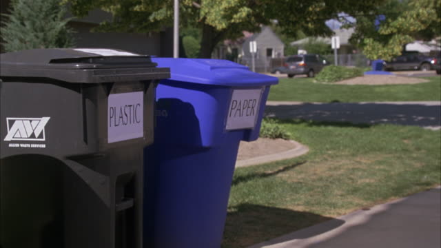 "MEDIUM ANGLE OF GARBAGE CANS LABELED ""PLASTIC"" AND ""PAPER"" FOR RECYCLING PURPOSES. LOCATED IN RESIDENTIAL AREA, PARK OR SCHOOLYARD IN SUBURBS."