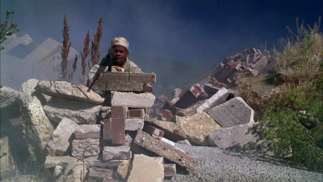 WIDE ANGLE OF SOLDIER OR GUERRILLA IN CAMOUFLAGE EATING HOT DOG AND HIDING IN  RUBBLE. HOLDING MACHINE GUN BEHIND BRICKS AND STONES. BATTLE. SMOKE. HUMOROUS.