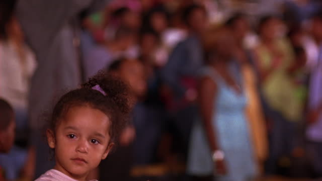 MEDIUM ANGLE OF  YOUNG GIRL OR TODDLER AT SPORTING EVENT, CONCERT, OR DANCE COMPETITION. SEE TEENAGE OR HIGH SCHOOL STUDENTS. CROWD CHEERS AND APPLAUDS.
