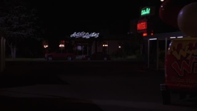 MEDIUM ANGLE OF LIGHTING STOREFRONT. SIGN READS 'ARTISTIC LIGHTING.' HOTEL OR MOTEL EXTERIOR TO RIGHT. CARGO TRUCK ENTERS PARKING LOT. CARS AND TRUCKS IN PARKING LOT.