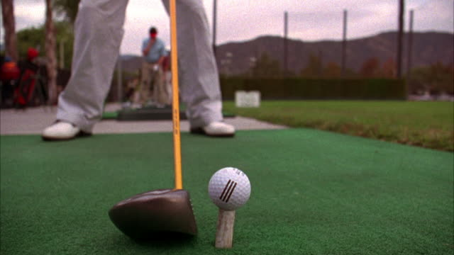 close angle of driving range. man in slacks and golf shoes swings driver golf club  back and forth then hits golf ball off deck. other golfers visible in bg. - golf swing stock videos & royalty-free footage