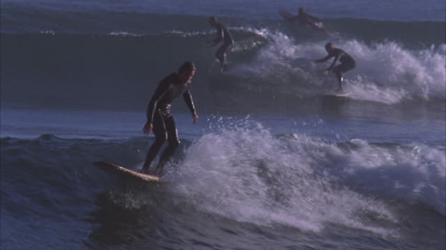 wide angle of surfer. man in bodysuit rides a wave and then pulls back at the break. other surfers visible in bg. pacific ocean. - 2004 stock videos & royalty-free footage