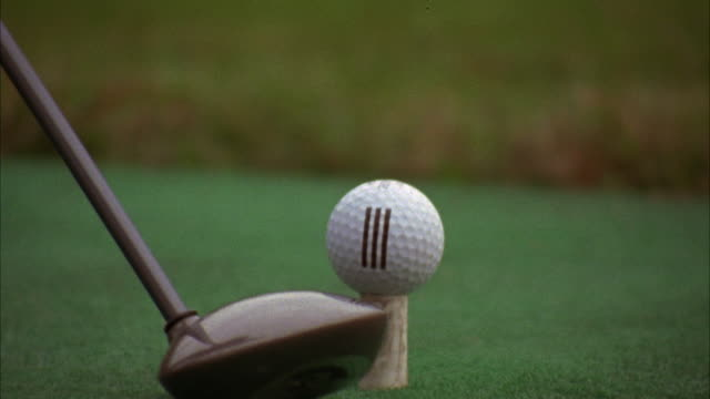 CLOSE ANGLE OF GOLF BALL. DRIVER GOLF CLUB SWINGS BACK AND FORTH UNTIL IT HIT BALL OFF DRIVING RANGE DECK.