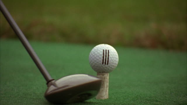 CLOSE ANGLE OF GOLF BALL. DRIVER GOLF CLUB SWINGS BACK AND FORTH UNTIL IT HITS BALL OFF DRIVING RANGE DECK.