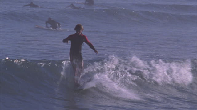 WIDE ANGLE OF SURFER. MAN IN BODYSUIT RIDES A WAVE AND THEN PULLS BACK AT THE BREAK. OTHER SURFERS VISIBLE IN BG. PACIFIC OCEAN.