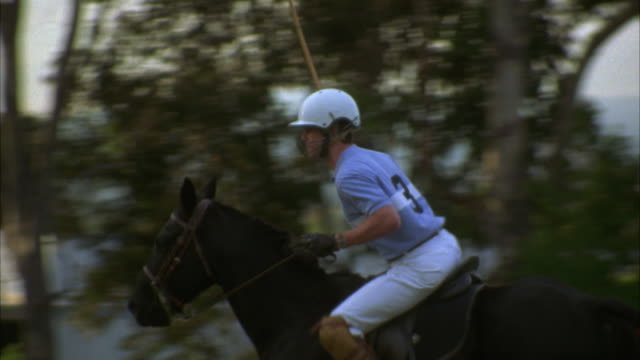 MEDIUM ANGLE OF POLO PLAYER WEARING A HELMET AND RIDING A BLACK HORSE. MAN WITH NUMBER '3' SHIRT SWINGS POLO STICK BACK AND FORTH ACROSS POLO GROUNDS.