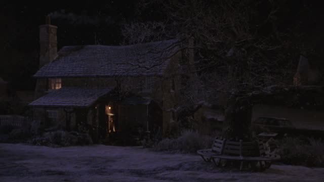 medium angle of quaint cottage or small house, snowy yard, fence, road. lights are on inside. snow is falling. - https点の映像素材/bロール