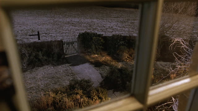 medium angle of quaint cottage or house yard. fence, gate with snow on ground. as seen from inside window of house. - コテージ点の映像素材/bロール