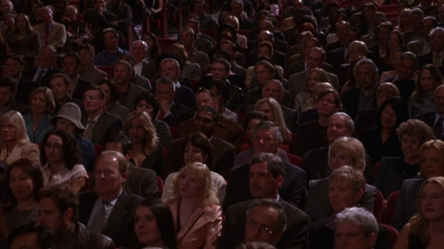 vidéos et rushes de wide angle of seated audience in auditorium or theater listening to unseen speaker. people in crowd laugh, clap and smile. could also be audience watching awards ceremony, play, or graduation. - public