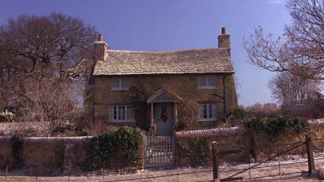 pan up of quaint english countryside house or cottage with fence, bare trees and some snow on ground. rural areas. - https点の映像素材/bロール