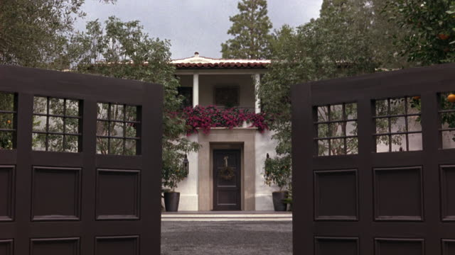 wide angle of wooden gate opening to reveal driveway leading to spanish style upper class mansion or house. pov moves forward, could be car driving through gate. - 門点の映像素材/bロール