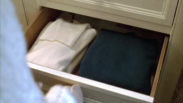 close angle of a woman's hands opening a drawer and taking out several sweaters. - drawer stock videos & royalty-free footage