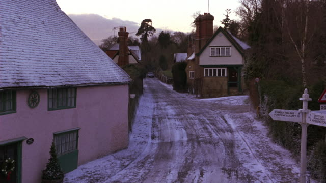 pan right to left shows black sedan driving on road through quaint english village. villagers walk on snow covered street, sidewalks past storefronts and houses. christmas wreaths hang above street. towns. - winter stock videos & royalty-free footage