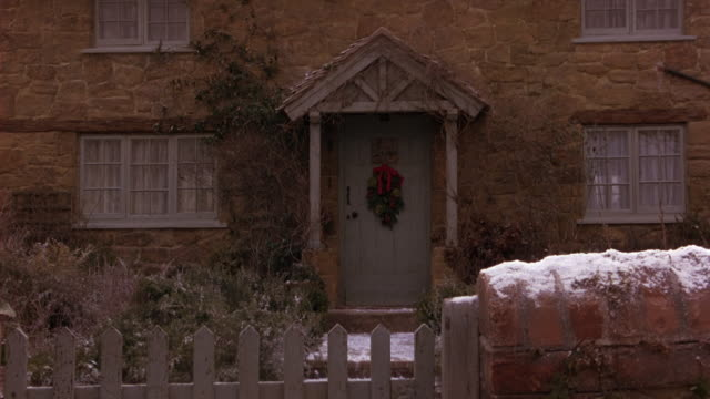 medium angle of two story english cottage with christmas wreath on front door. brick gate and wooden fence in front of stone house has light dusting of snow. - www stock videos & royalty-free footage