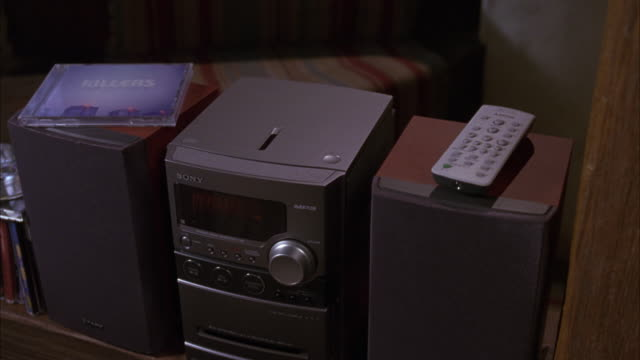 "CLOSE ANGLE OF A SONY CD PLAYER.  TWO LARGE SPEAKERS.  A REMOTE CONTROL ON ONE SPEAKER, A ""KILLERS"" CD ON THE OTHER."