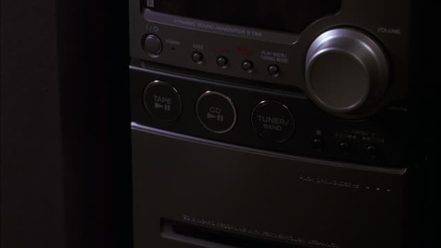 "CLOSE ANGLE OF A CD PLAYER STEREO.  A WOMAN'S FINGER PRESSES THE ""PLAY"" BUTTON."