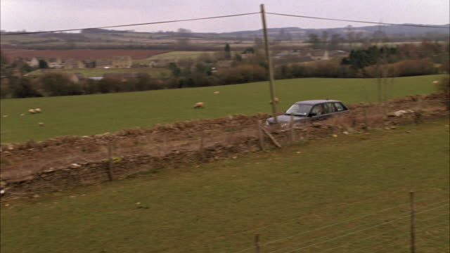 PAN RIGHT TO LEFT OF RANGE ROVER DRIVING PAST FIELDS, FENCES, COUNTRYSIDE WITH STONE WALL ALONGSIDE PASTURE. CARS. RURAL AREAS.