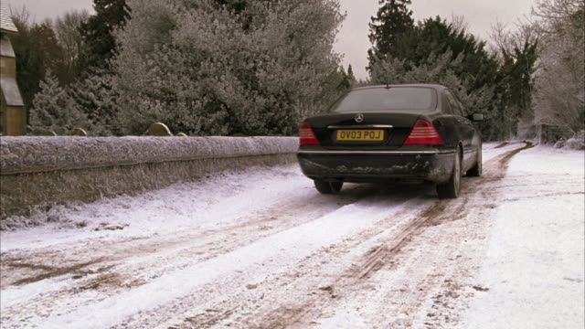 wide angle of stone wall next to road, black car drives away through snow-covered trees, winter forest. european license plates. mercedes - mercedes benz stock videos and b-roll footage