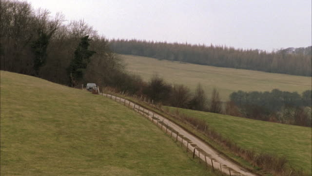 PAN LEFT TO RIGHT OF FIELD WITH FENCE. RANGE ROVER DRIVING PAST FIELDS. COUNTRYSIDE. RURAL AREAS. CARS.