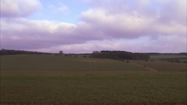 WIDE ANGLE OF FIELD RANGE ROVER DRIVING PAST COUNTRYSIDE. SKY IS CLOUDY. RURAL AREAS. CARS.