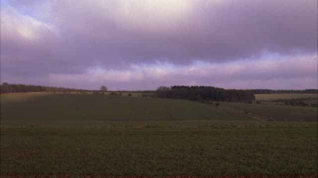 WIDE ANGLE OF FIELD. RANGE ROVER DRIVING PAST COUNTRYSIDE. SKY IS CLOUDY. RURAL AREAS. CARS.