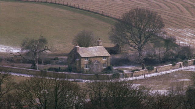 wide angle of quaint cottage or small house, slight snow in yard, fenced field, road. english countryside, europe. rural areas. - https点の映像素材/bロール