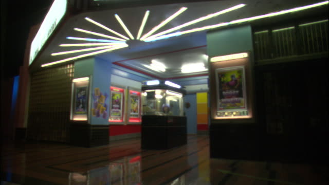 MEDIUM ANGLE OF FRONT OF MOVIE THEATRE. SEE WOMAN SITTING IN TICKET BOOTH IN CENTER OF THEATRE ENTRANCE. SEE MOVIE POSTERS FLANKING ENTRANCE.