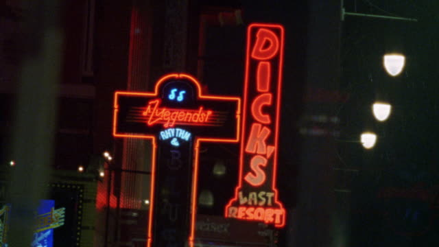 "neon signs on beale street in memphis, tennessee. it is raining. fade in to ""legends "" and ""dick's last resort."" pan right to ""have a nice day cafe,"" ""down home ice works"" and ""hard rock cafe."" pan up hard rock's guitar logo. restaurants. - fade in video transition stock videos & royalty-free footage"