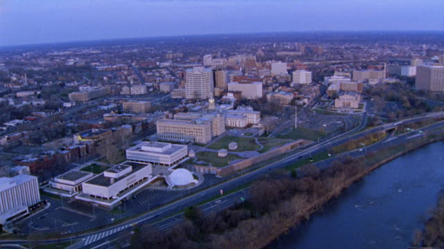 AERIAL OF DOWNTOWN TRENTON WITH THE DELAWARE RIVER IN THE BG.  A SMALL EAST COAST CITY. THE CAMERA ZOOMS IN ON THE NEW JERSEY STATE CAPITOL BUILDING. DOMED BUILDING, GOVERNMENT BUILDING.