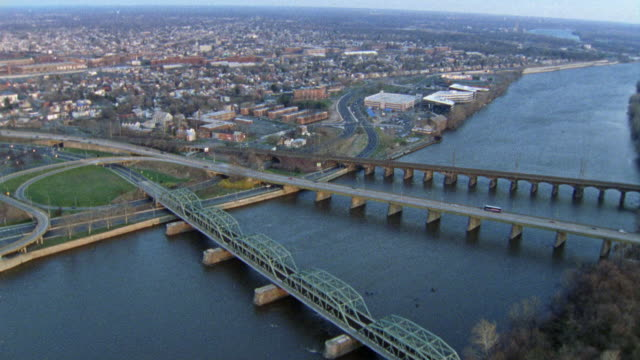 AERIAL OF THREE BRIDGES OVER THE DELAWARE RIVER, THE CITY OF TRENTON IN THE BACKGROUND.
