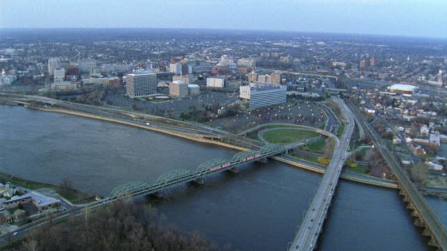 "AERIAL OF A BRIDGE OVER THE DELAWARE RIVER, THE CITY OF TRENTON IN THE BACKGROUND. A SIGN ON THE BRIDGE READS ""TRENTON MAKES, THE WORLD TAKES""."