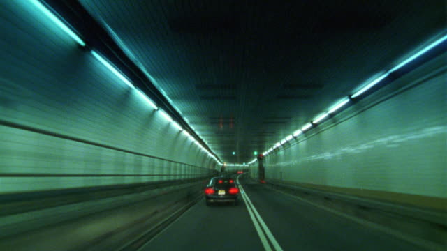 wide angle driving pov of the inside of a tunnel.  long fluorescent light fill the tunnel with green light. probably the holland tunnel. - vidvinkel bildbanksvideor och videomaterial från bakom kulisserna