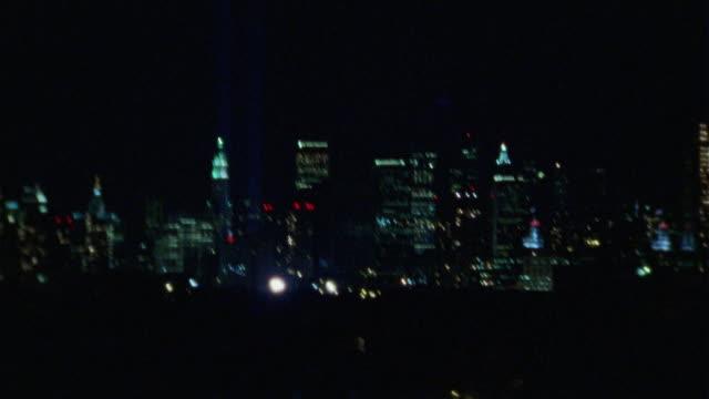 HAND HELD DRIVING POV OF THE NEW YORK CITY SKYLINE AND THE WORLD TRADE CENTER MEMORIAL LIGHT ART INSTALLATION.