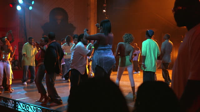 WIDE ANGLE OF YOUNG WOMEN, MEN DANCING IN BAR, DANCE CLUB, TAVERN OR NIGHTCLUB.  MUSIC. RACK FOCUS IN AND OUT, BLURRY.