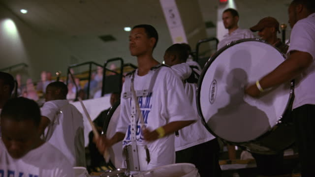 hand held of an audience or crowd standing, watching, and applauding a performance. likely college students; could be a sporting event or pep rally. - marching band stock videos & royalty-free footage