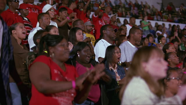 hand held of an audience or crowd standing, watching, and applauding a performance. likely college students; could be a sporting event or pep rally. arena, stadium, or auditorium. crowd clapping, dancing. - auditorium stock videos and b-roll footage