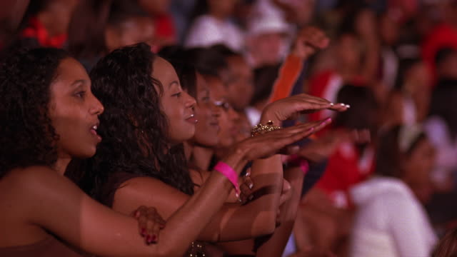 medium angle of  girls at sporting event, concert, or dance competition. crowd cheers and applauds. could be reaction shot. see other members of audience dancing and singing along. - auditorium stock videos & royalty-free footage