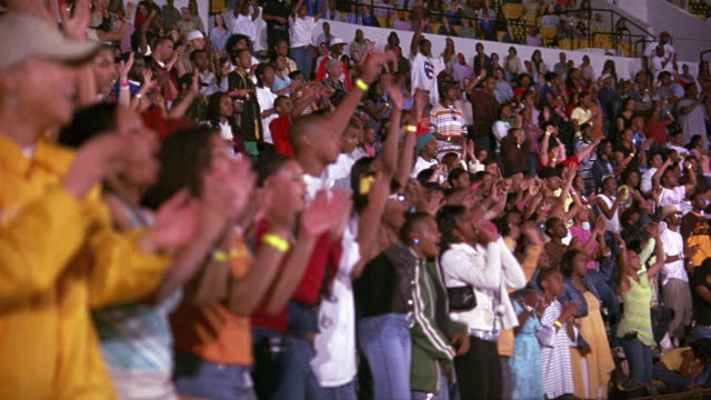 HAND HELD OF AN AUDIENCE OR CROWD STANDING, WATCHING, AND APPLAUDING A PERFORMANCE. LIKELY COLLEGE STUDENTS; COULD BE A SPORTING EVENT OR PEP RALLY. ARENA, STADIUM, OR AUDITORIUM. CROWD CLAPPING, DANCING.