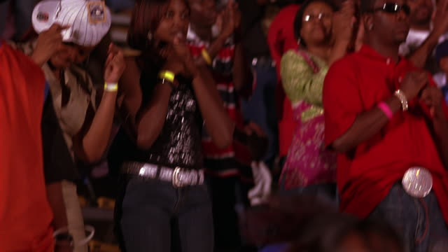 medium angle of  girls at sporting event, concert, or dance competition. see teenage or high school students. boy swirling shirt in hand. - auditorium stock videos & royalty-free footage