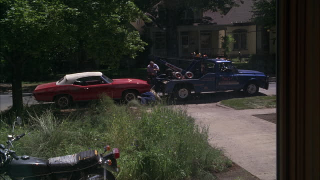 WIDE ANGLE OF CONVERTIBLE ROADSTER CAR TOWED BY TOW TRUCK FROM CURB ON STREET IN RESIDENTIAL AREA. HONDA MOTORCYCLE PARKED IN OVERGROWN TALL GRASS IN FRONT YARD. POV FROM WINDOW OF HOUSE. CURTAINS IN FG.