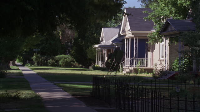wide angle of middle class houses along a sidewalk in residential areas or neighborhood. trees and shrubs. iron fence surrounding unkempt lawn in fg. - middle class stock videos and b-roll footage