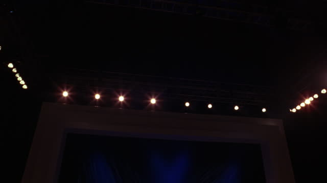 WIDE ANGLE LOOKING UP AT MUSIC OR DANCE STAGE AT CONCERT. SEE LIGHTING RIG AND CURTAINS. COULD BE THEATER LIGHTS.