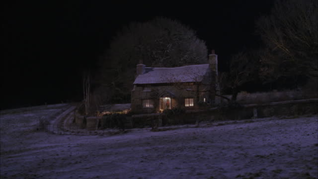 wide angle of quaint cottage or house with wreath on door, smoke coming from chimney, snow falling. winter, christmas. rural areas. - landhaus stock-videos und b-roll-filmmaterial