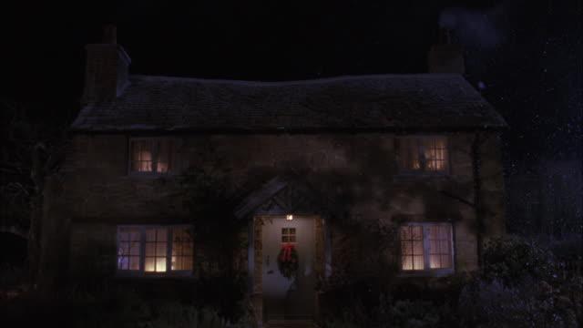 vídeos de stock, filmes e b-roll de medium angle of quaint cottage or house with wreath on door, smoke coming from chimney, snow falling. winter, christmas. - cabana casa