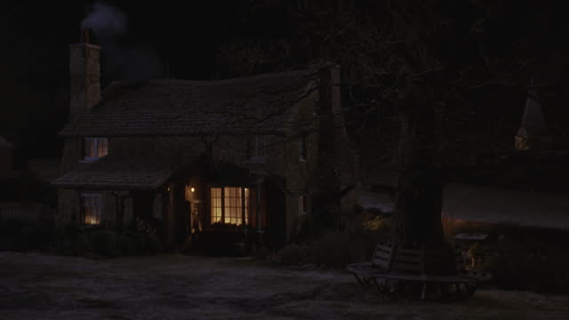 medium angle of quaint cottage or small house, snowy yard, fence, road. lights are on inside. - https点の映像素材/bロール